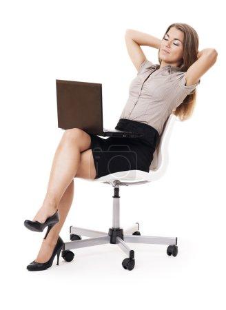 Foto de Mujer de negocios con portátil relajante en la silla de la oficina - Imagen libre de derechos