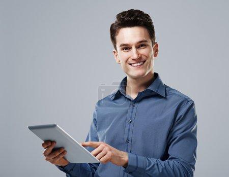 Photo pour Homme heureux utilisant une tablette numérique - image libre de droit