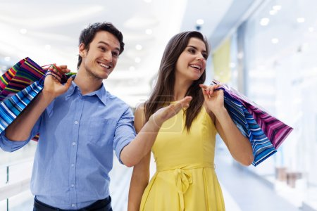Photo for Smiling man showing something woman in the shopping mall - Royalty Free Image