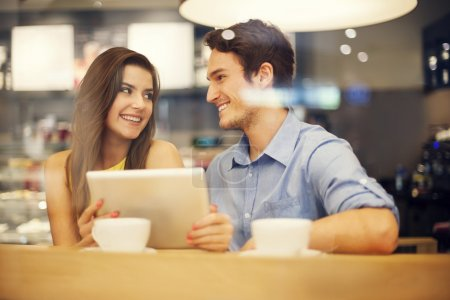Photo for Flirting couple in cafe using digital tablet - Royalty Free Image