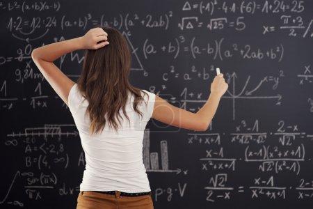 Photo pour Jeune femme regardant le problème de maths sur tableau noir - image libre de droit