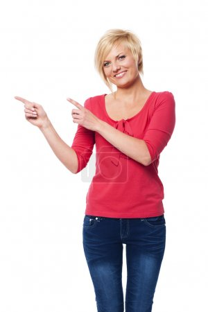 Photo for Blonde woman pointing at copy space - Royalty Free Image