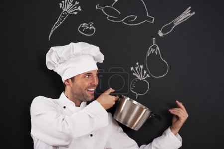 Photo for Handsome chef catching ingredients for soup - Royalty Free Image