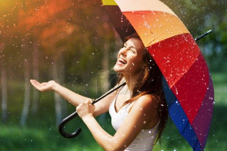 Photo for Laughing woman with umbrella checking for rain - Royalty Free Image