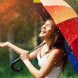 Laughing woman with umbrella checking for rain...