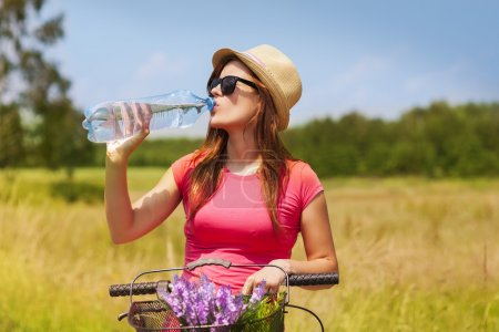 Photo for Active woman with bike drinking cold water - Royalty Free Image