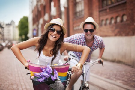 Photo for Happy couple cycling in the city - Royalty Free Image