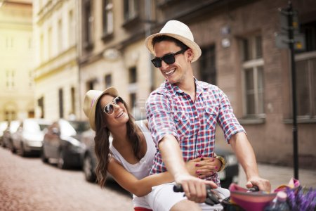 Photo pour Beau homme prenant sa petite amie sur le porte-vélos - image libre de droit