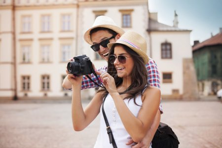 Photo for Cute couple looking on their photos on camera - Royalty Free Image