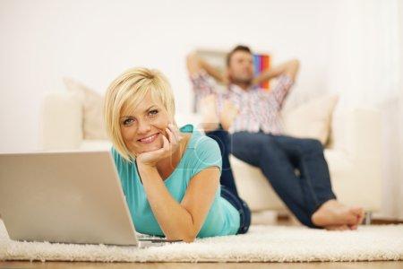 Photo pour Belle femme blonde utilisant un ordinateur sur le tapis - image libre de droit