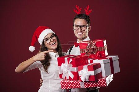 Photo pour Couple nerd souriant montrant cadeau de Noël - image libre de droit