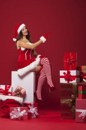 Photo pour Père Noël sexy avec beaucoup de cadeaux de Noël pointant vers l'espace de copie rouge - image libre de droit