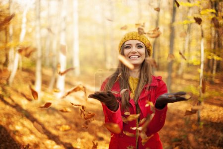 Photo for Happy woman throwing leaves - Royalty Free Image