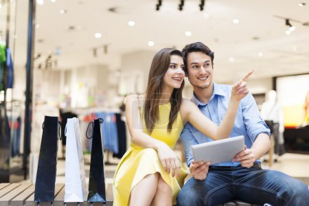 Photo for Couple in shopping mall using digital tablet - Royalty Free Image