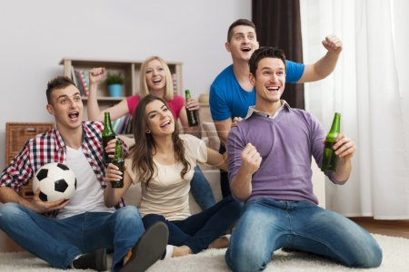 Friends enjoying soccer in TV