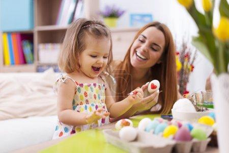 Photo pour Mère aimante et son bébé peignant des œufs de Pâques - image libre de droit