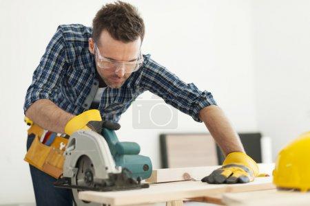 Carpenter sawing wood board