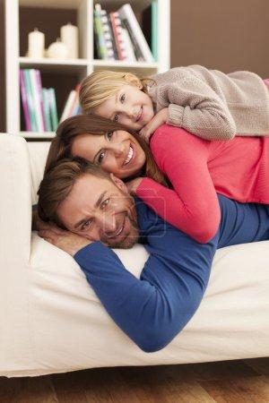 Photo pour Heureuse famille allongée sur le canapé - image libre de droit