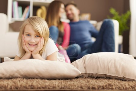 Photo for Portrait of smiling girl relaxing on carpet in living room - Royalty Free Image