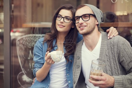 Photo for Young fashion couple drinking coffee outside of cafe - Royalty Free Image
