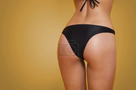 Female buttocks in black bikini
