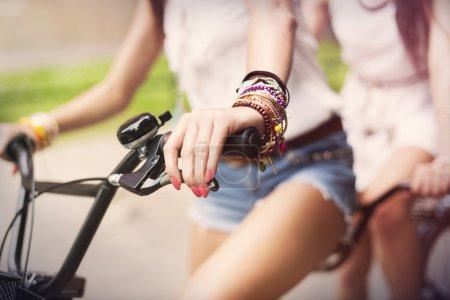 Foto de Cerca de boho chicas montando en bicicleta - Imagen libre de derechos