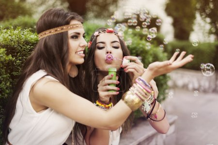 Photo for Hippie two beautiful girls blowing bubbles - Royalty Free Image