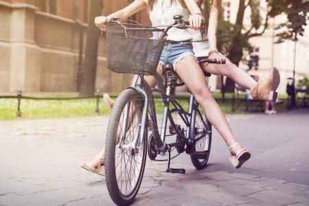 Photo pour Partie des jambes des filles boho pendant le vélo en tandem - image libre de droit