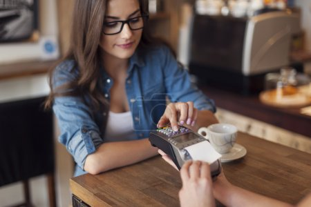 Woman paying for cafe by credit card