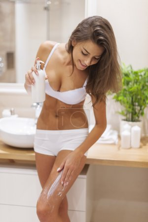 Young woman applying body lotion...