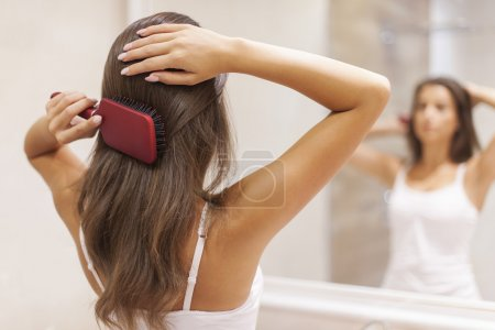 Photo pour Jeune femme brossant des cheveux sains devant un miroir - image libre de droit