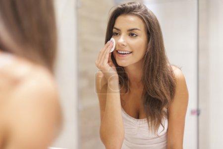 Photo pour Belle femme brune démaquillant son visage - image libre de droit