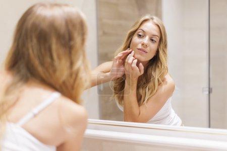 Photo pour Femme blonde a des problèmes avec la peau sur le visage - image libre de droit