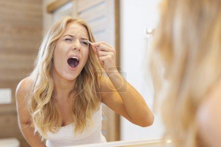 Woman tweezing eyebrows