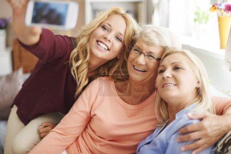 Blonde girl taking selfie with mom and grandma...