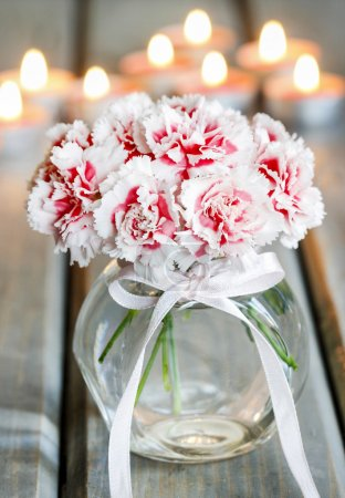 Bouquet of carnation flowers in glass vase on wooden table