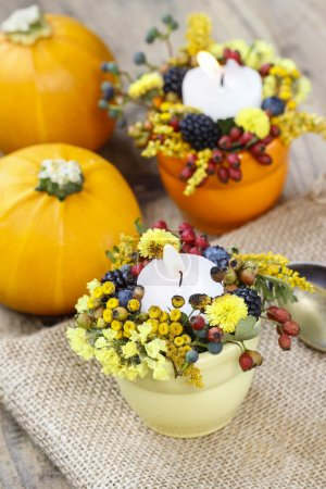 Candle holder decorated with autumn flowers and other plants