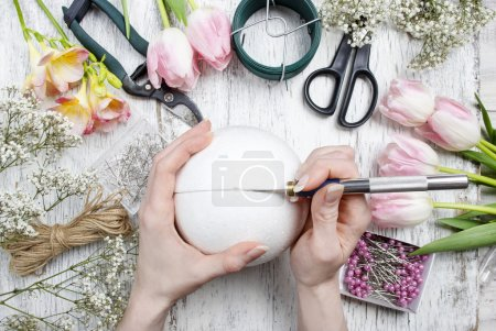 Florist workplace: woman making floral arrangements with polysty