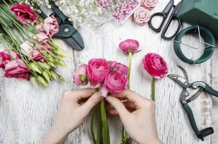 Florist at work. Woman making beautiful bouquet of pink persian