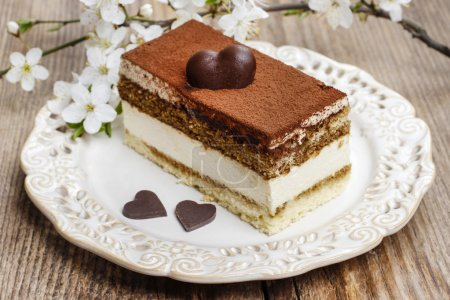Tiramisu cake on white plate. Blossom apple branch in the backgr