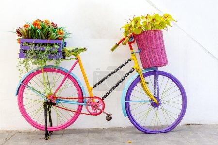 Foto de Vieja bicicleta retro elegante con ramo de flores en la cesta - Imagen libre de derechos
