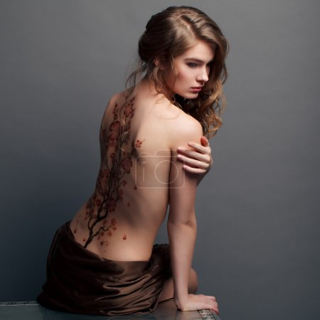 Beautiful girl with a pattern on the back