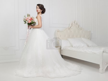Beautiful sensual brunette with elegant hairstyle. Wedding dress
