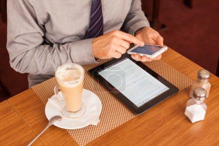 Foto de Empresario tomando café en café y mediante teléfono móvil - Imagen libre de derechos