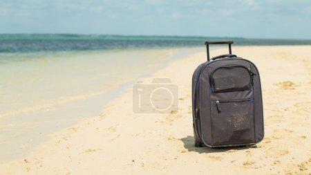 Photo pour Valise de voyage sur la plage - image libre de droit