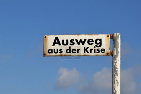 An old street sign with the words out of the crisi...