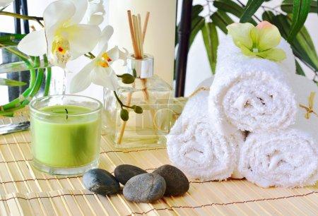 Photo pour Bel arrangement d'articles de spa, y compris : bougies, fleurs, parfum, serviettes blanches et pierres chaudes - image libre de droit