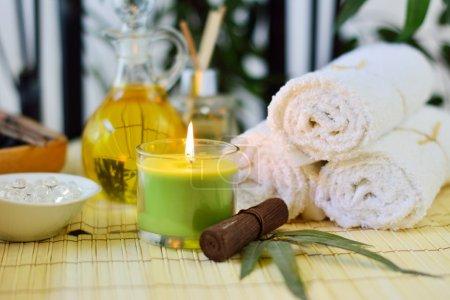 Photo pour Lits de spa, bougies, serviettes blanches, bambou, huiles, roches et parfums - image libre de droit