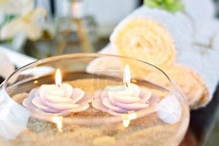 Photo pour Spa bougies flottantes dans le sable avec serviettes blanches et fleurs - image libre de droit