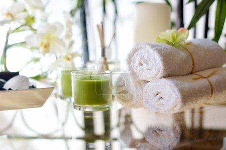 Photo pour Cadre de spa avec des bougies vertes serviettes blanches, roches de spa, dollar de sable, fleurs, & parfum - image libre de droit